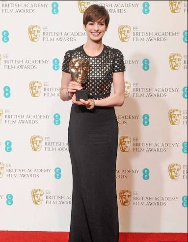 Anne Hathaway wore a Burberry gown with studded bodice and carried an Anya Hindmarch clutch.
