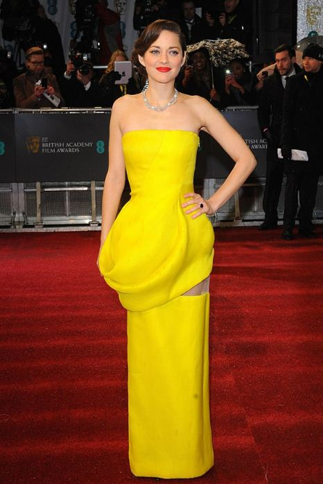 Marion Cotillard in a Dior Couture canary yellow strapless gown with a Chopard diamond necklace and ring.